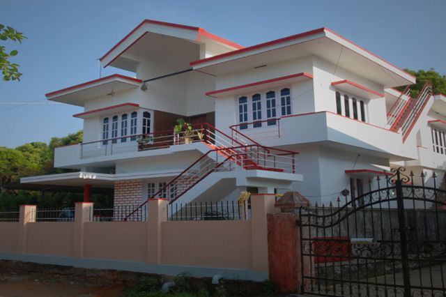 Large Multiple Level White House With Red Roof And Trim Behind A Wrought Iron Entry Sai Sadan Homestay
