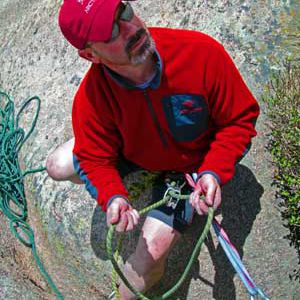 Bill Springer holding a belay rope and paying close attention to climbers.