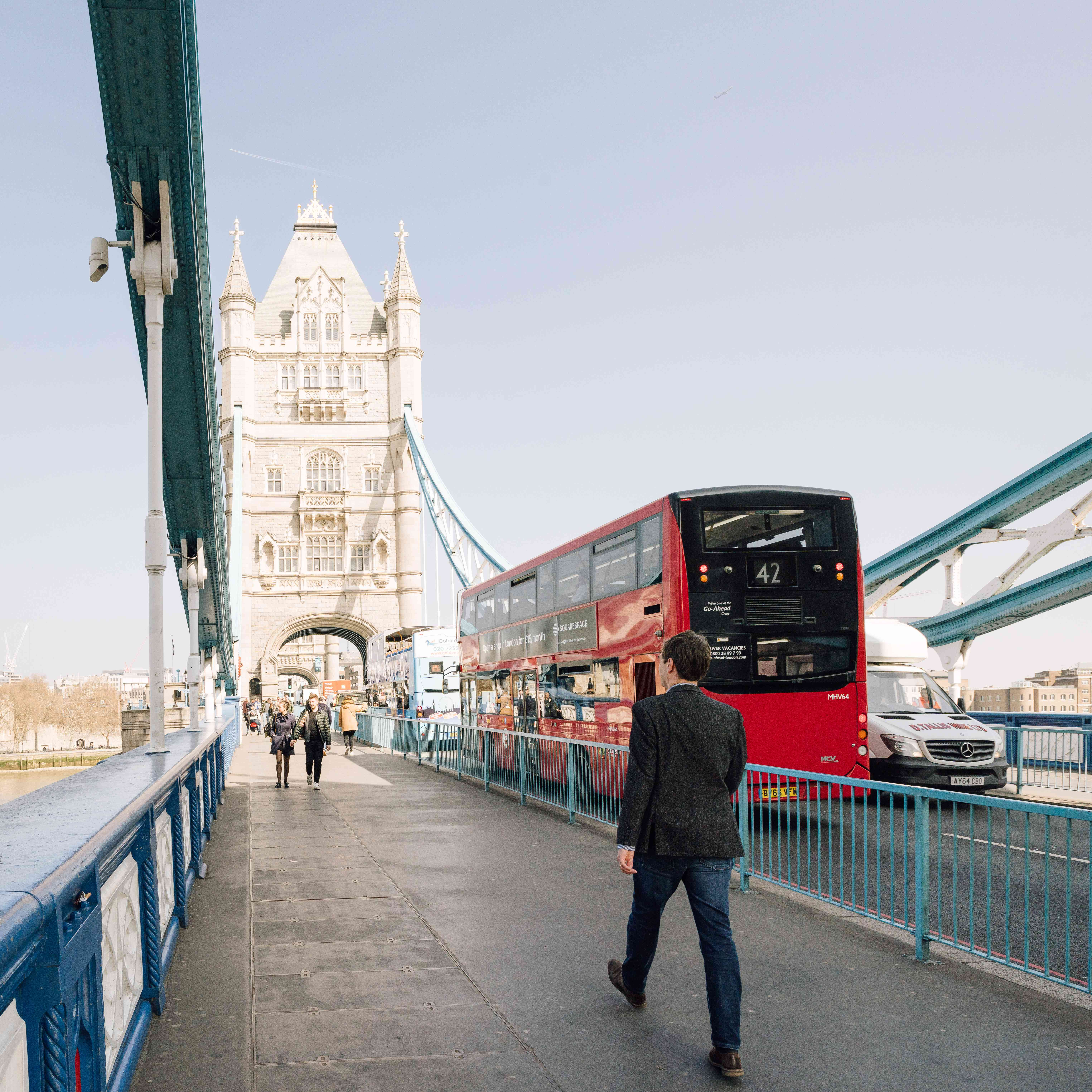 A double decker red bus crossing tower bridge