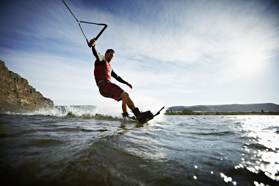 Man carving turn on wakeboarding view from water