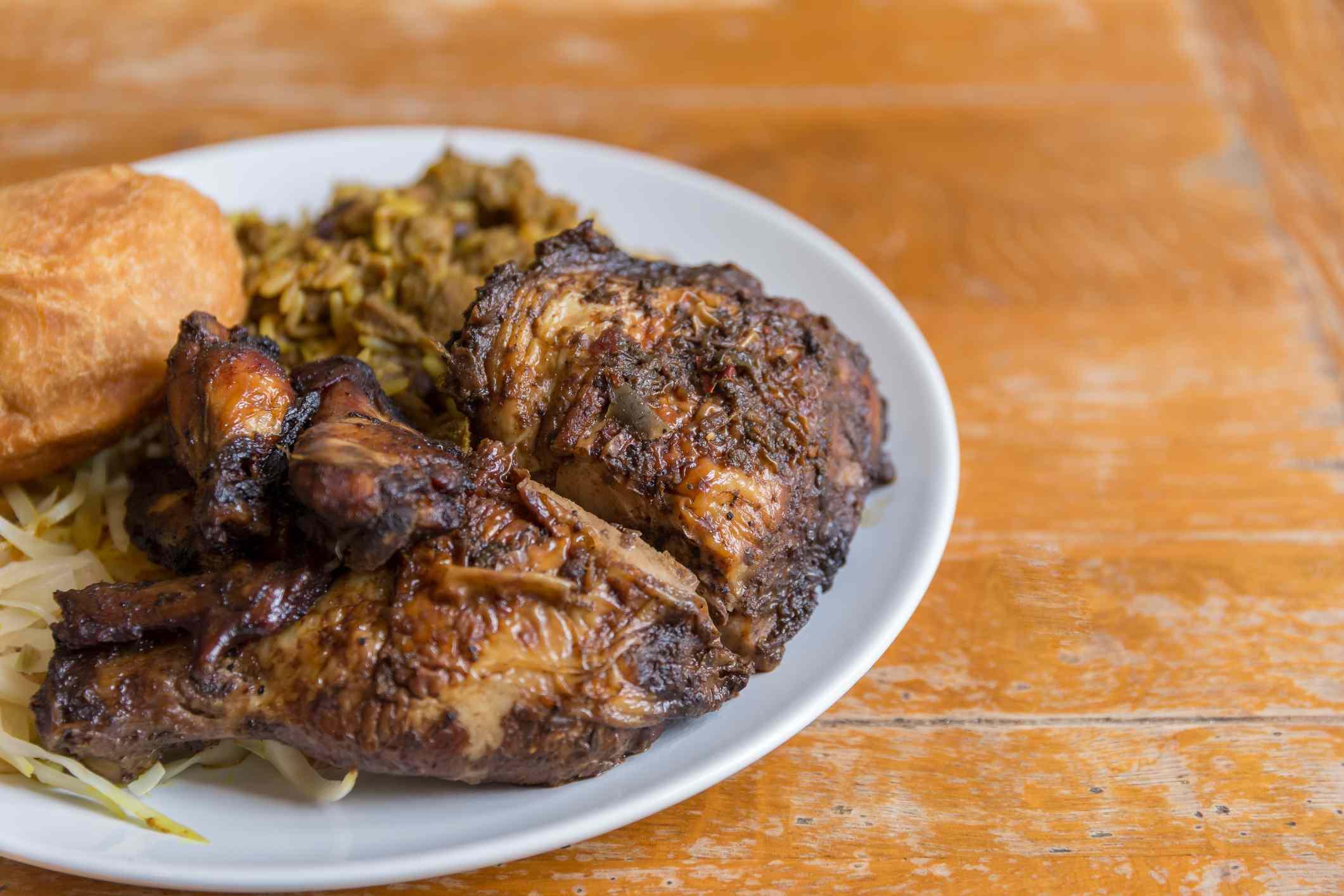 Jerk chicken alongside curry goat and fried dumpling
