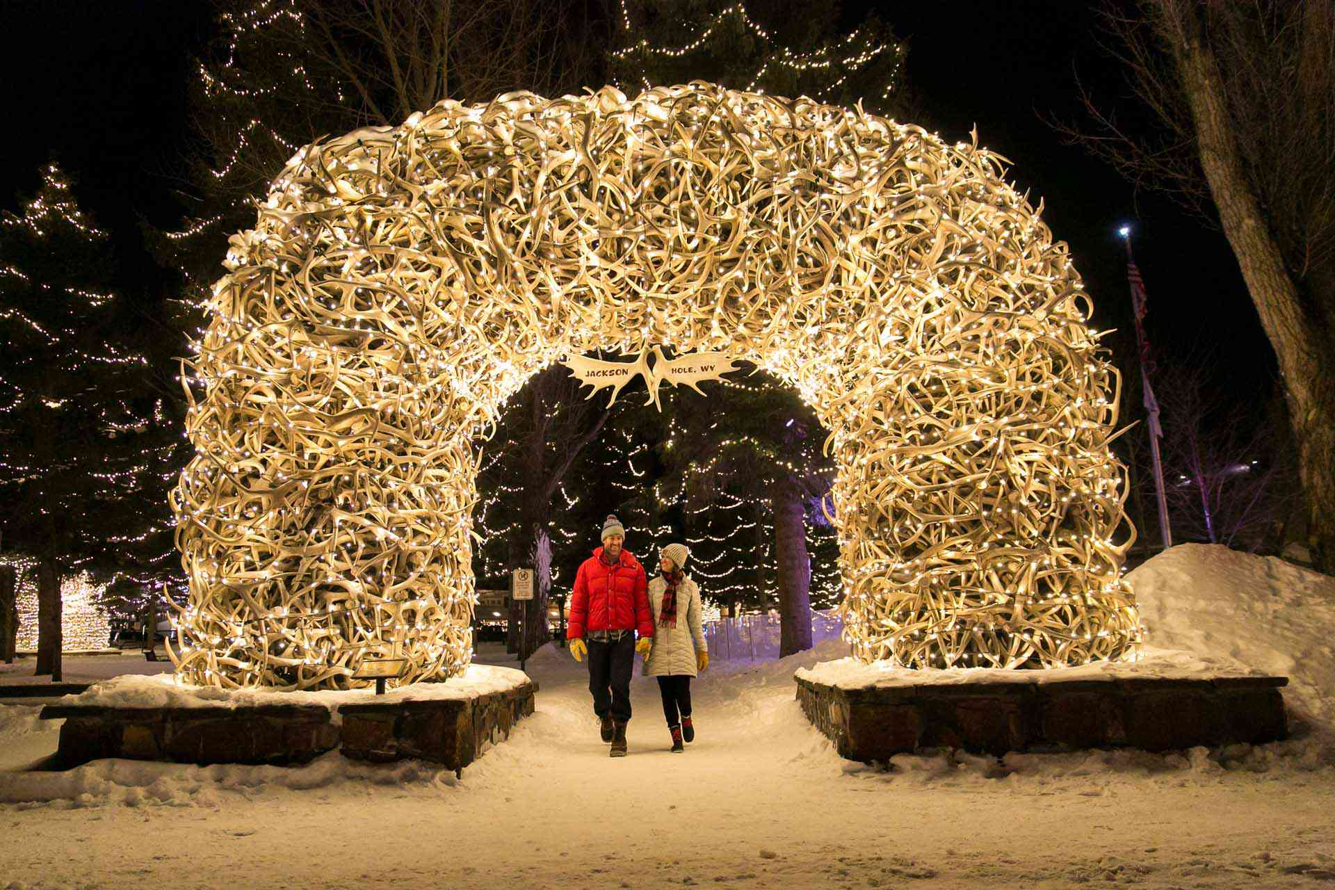 Couple walking underneath an arch made of antlers with lights around it. It is nighttime during winter