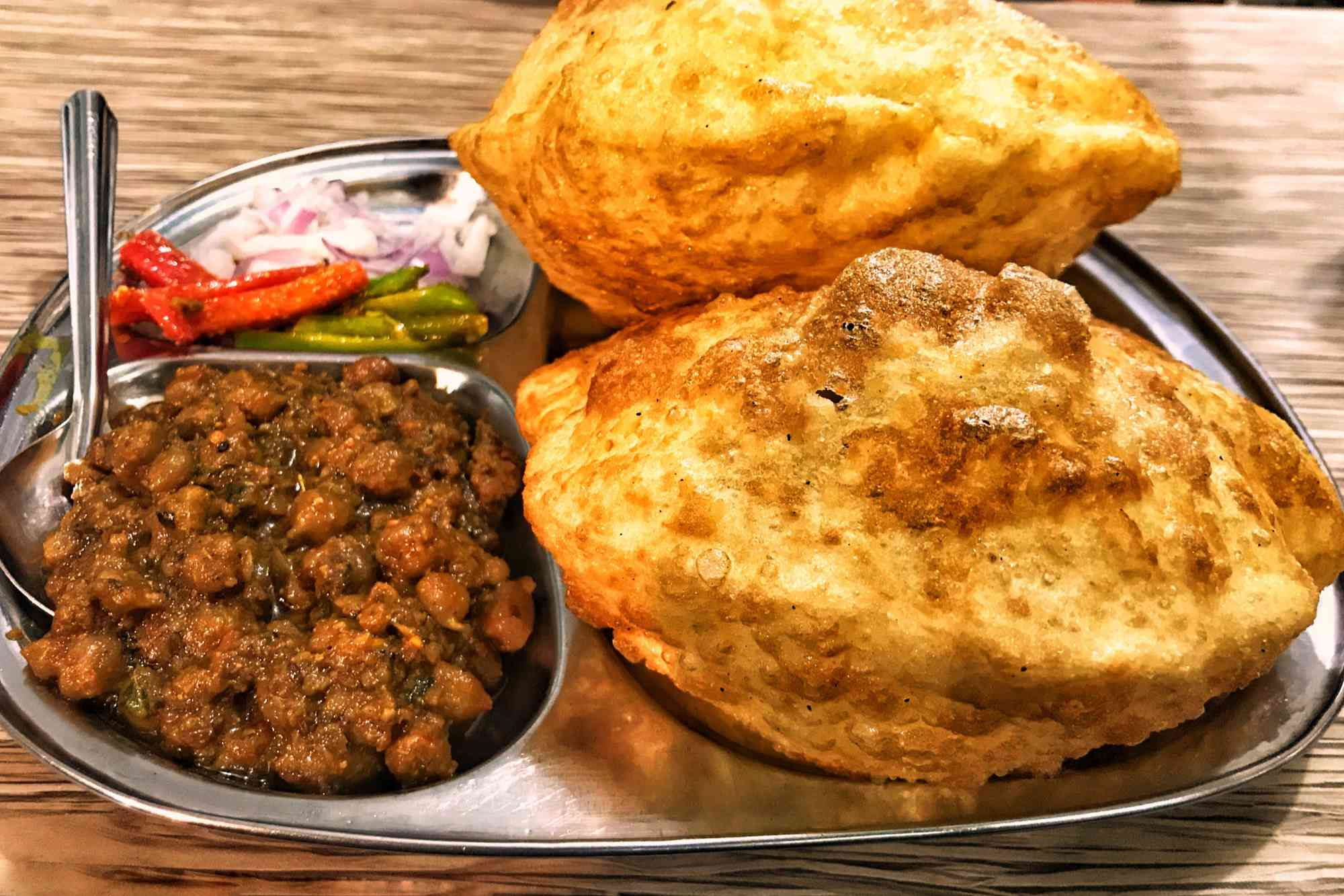 Chole bature on a metal tray with channa masala and pickled veggies
