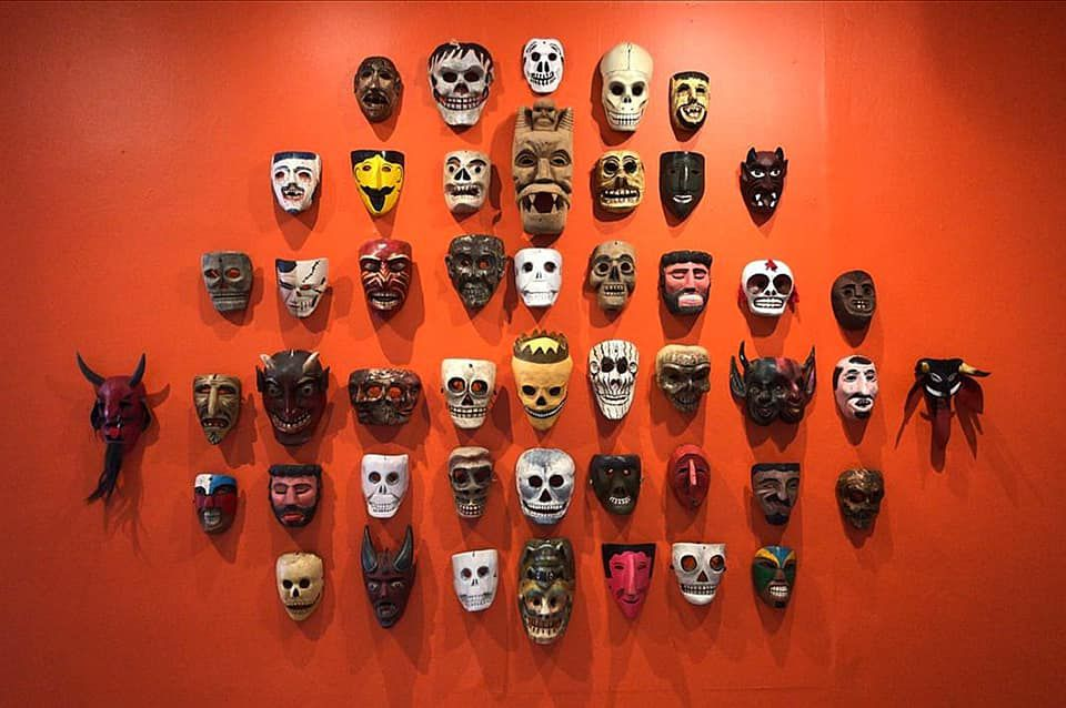 Collection of Masks mounted on an orange wall at the Museo Nacional de Culturas Populares