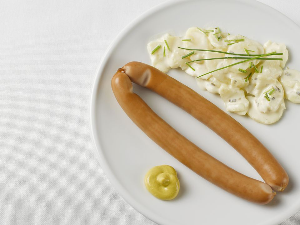 Pair of sausages with potato salad and mustard in plate on white background