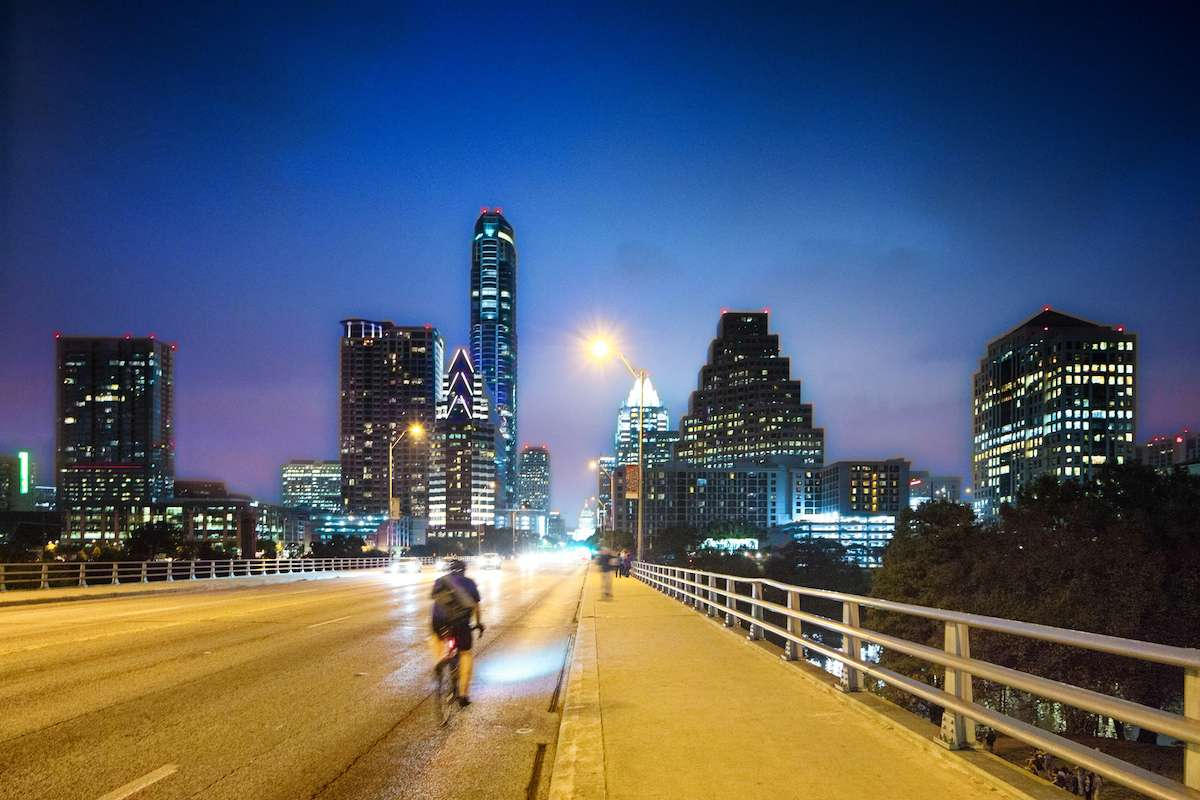 A cyclist rides towards downtown Austin on South Congress Ave.