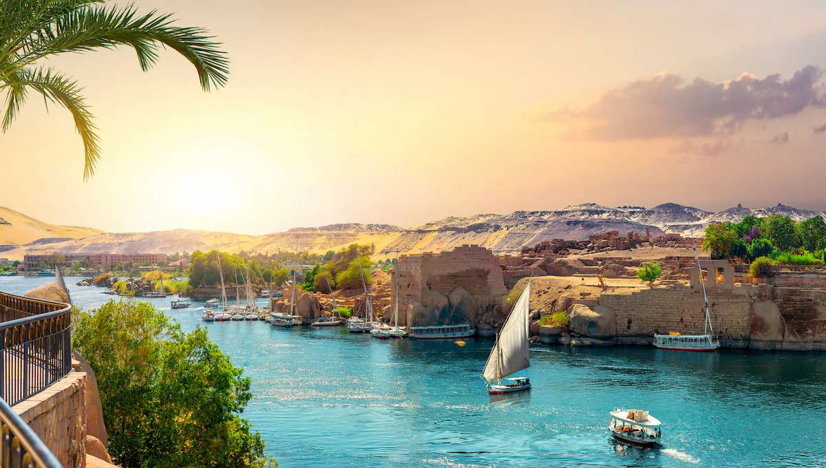 Small ships sail along a narrow stretch of the Nile river with ruins in the background.