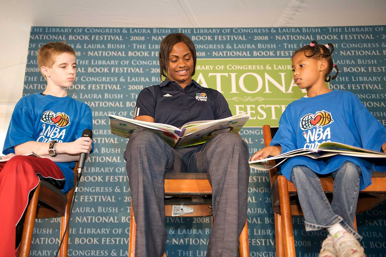 Woman reading with two kids on stage at National Book Festival