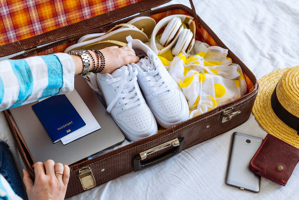 Woman placing white shoes in a vintage suitcase