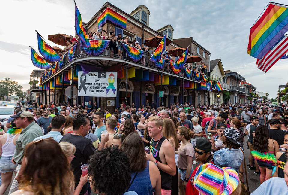 Crowds on Bourbon St with rainbow flags