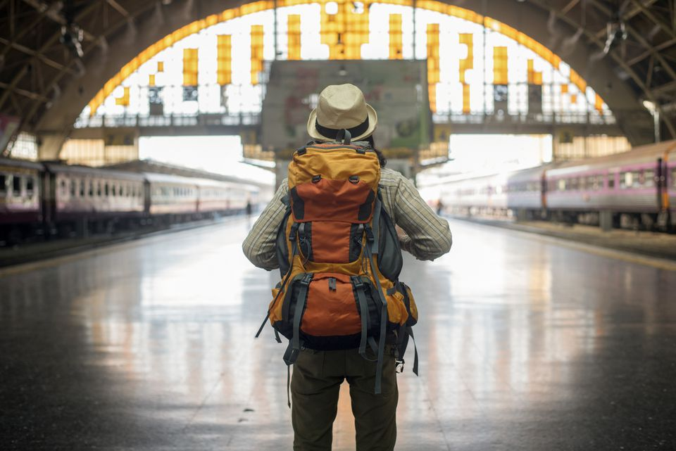 A backpacker in Asia stands in a train station