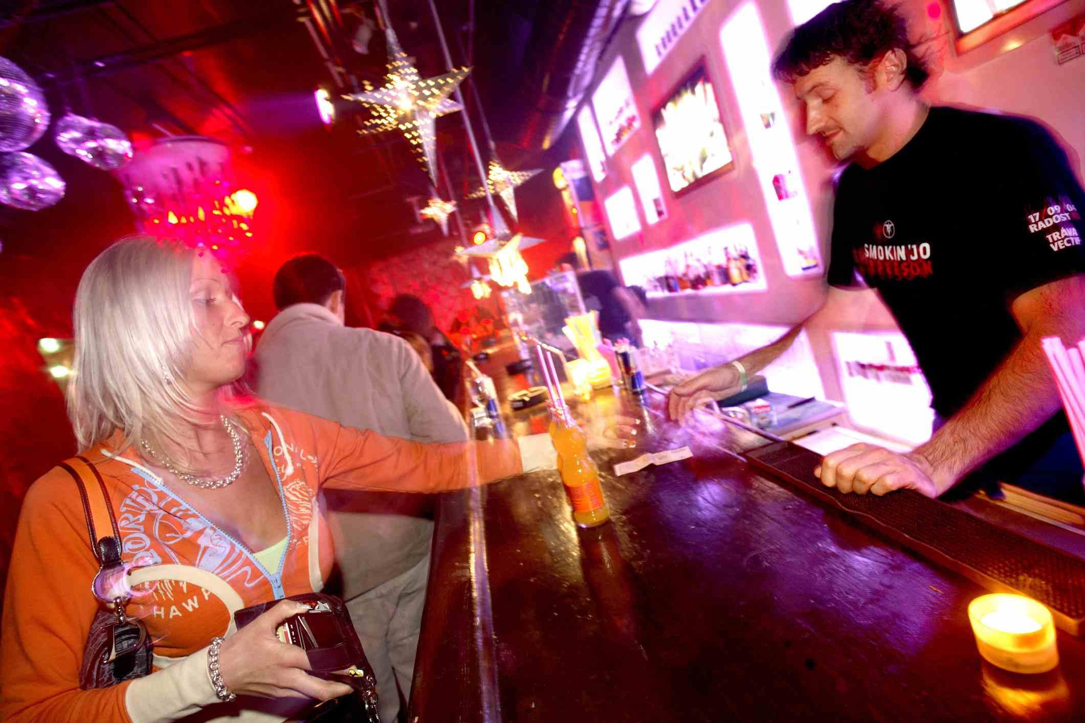Mujer que pide una bebida en el club nocturno de Praga
