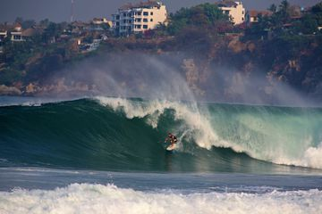 A surfer taking on a giant wave at Zicatela beach