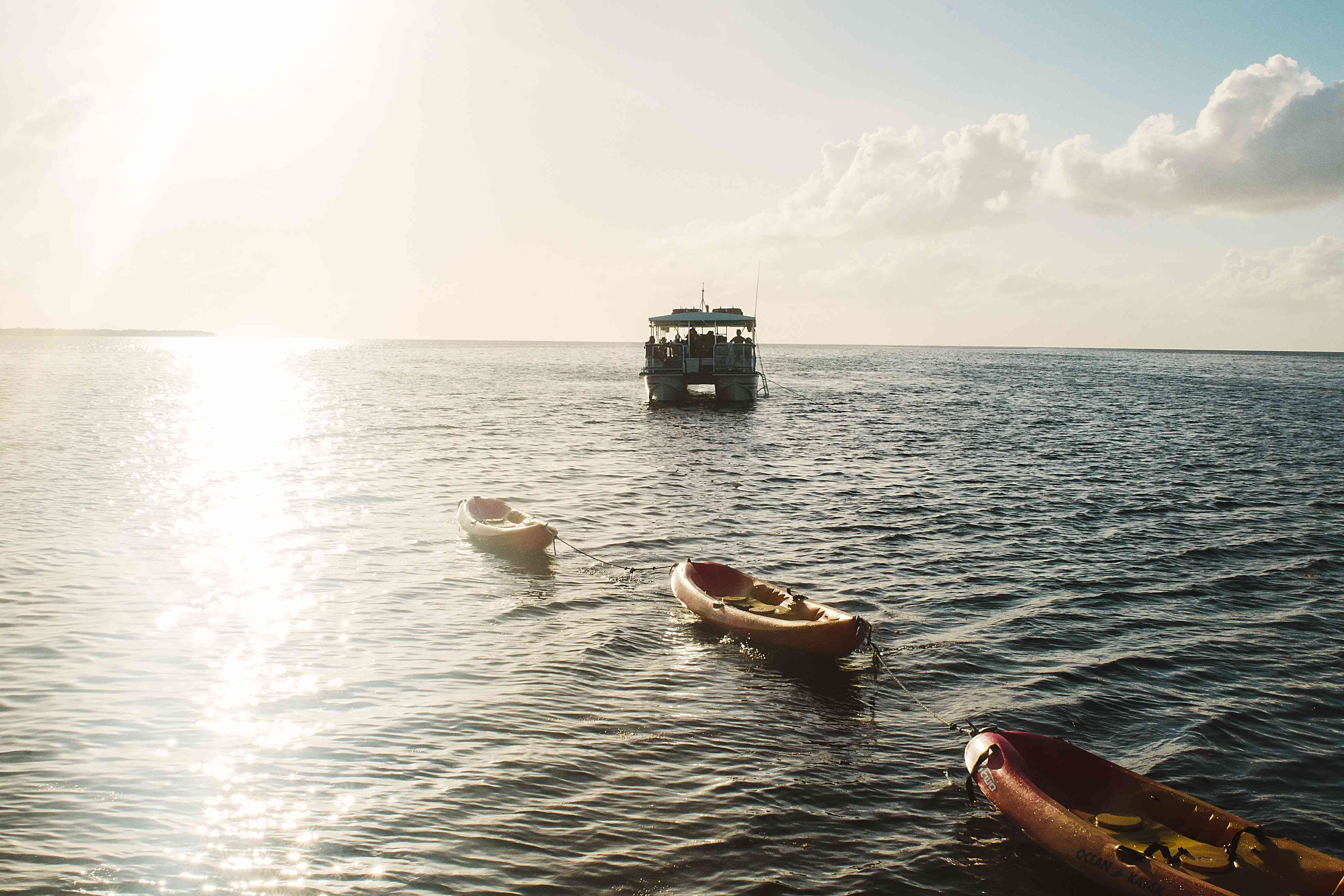 Tour boat with kayaks trailing behind at sunset