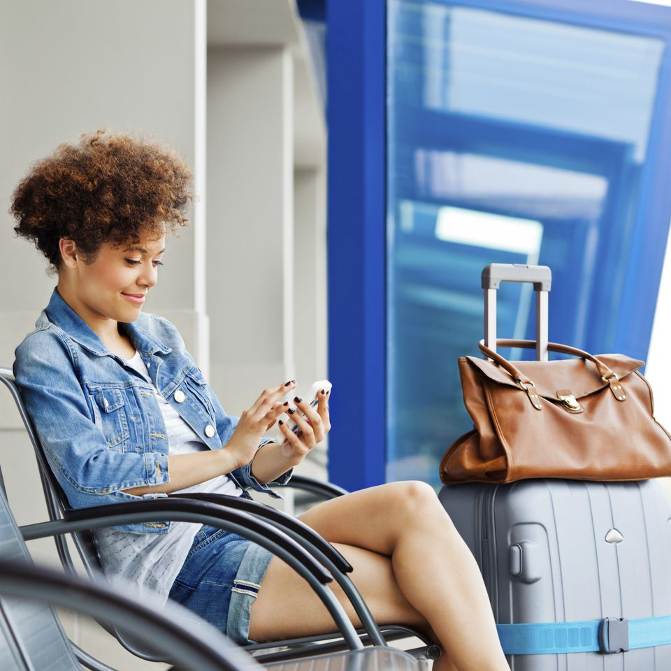 Young woman using cell phone while waiting for flight