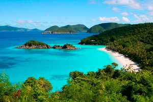 Bright blue Caribbean waters with a beach and tree covered islands