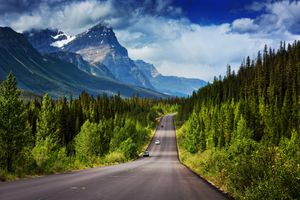 Two-lane famous Icefields Parkway between Lake Louise and Jasper, Alberta, with snowcapped mountains looming above in summer