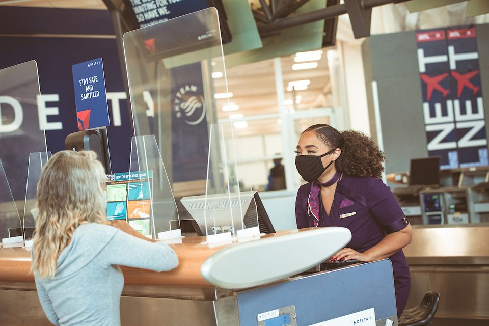 Delta masked ticketing agent with passenger