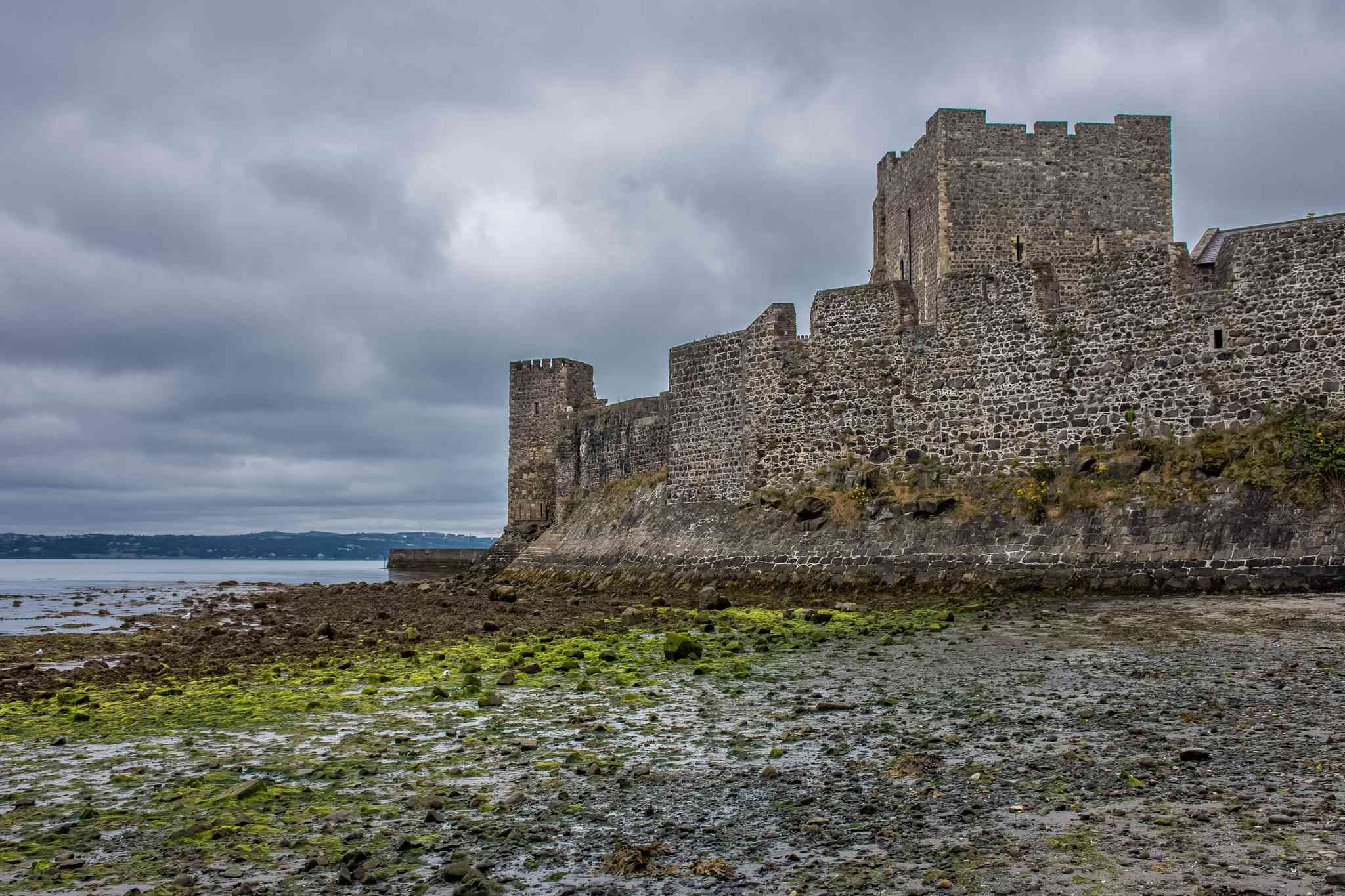 stone walls of carrickfergus castle on marshy land with belfast lough in the background