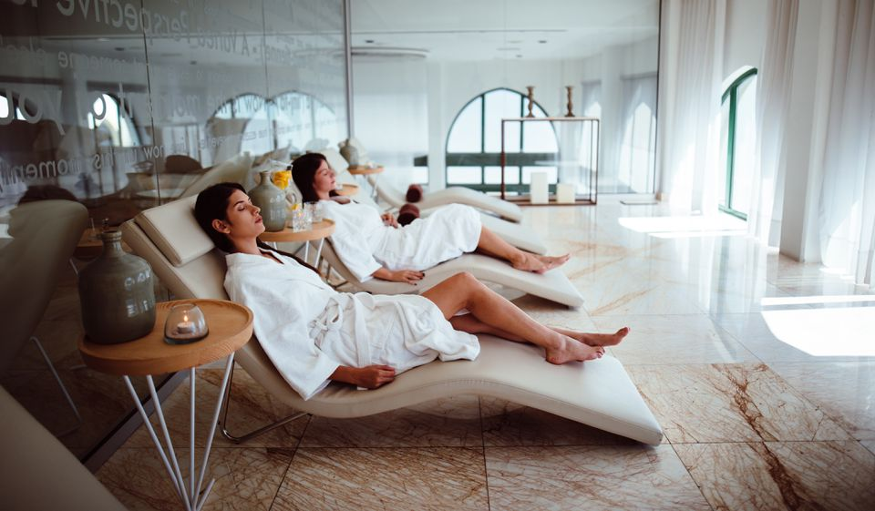 Young women in white robes relaxing at beauty spa centre