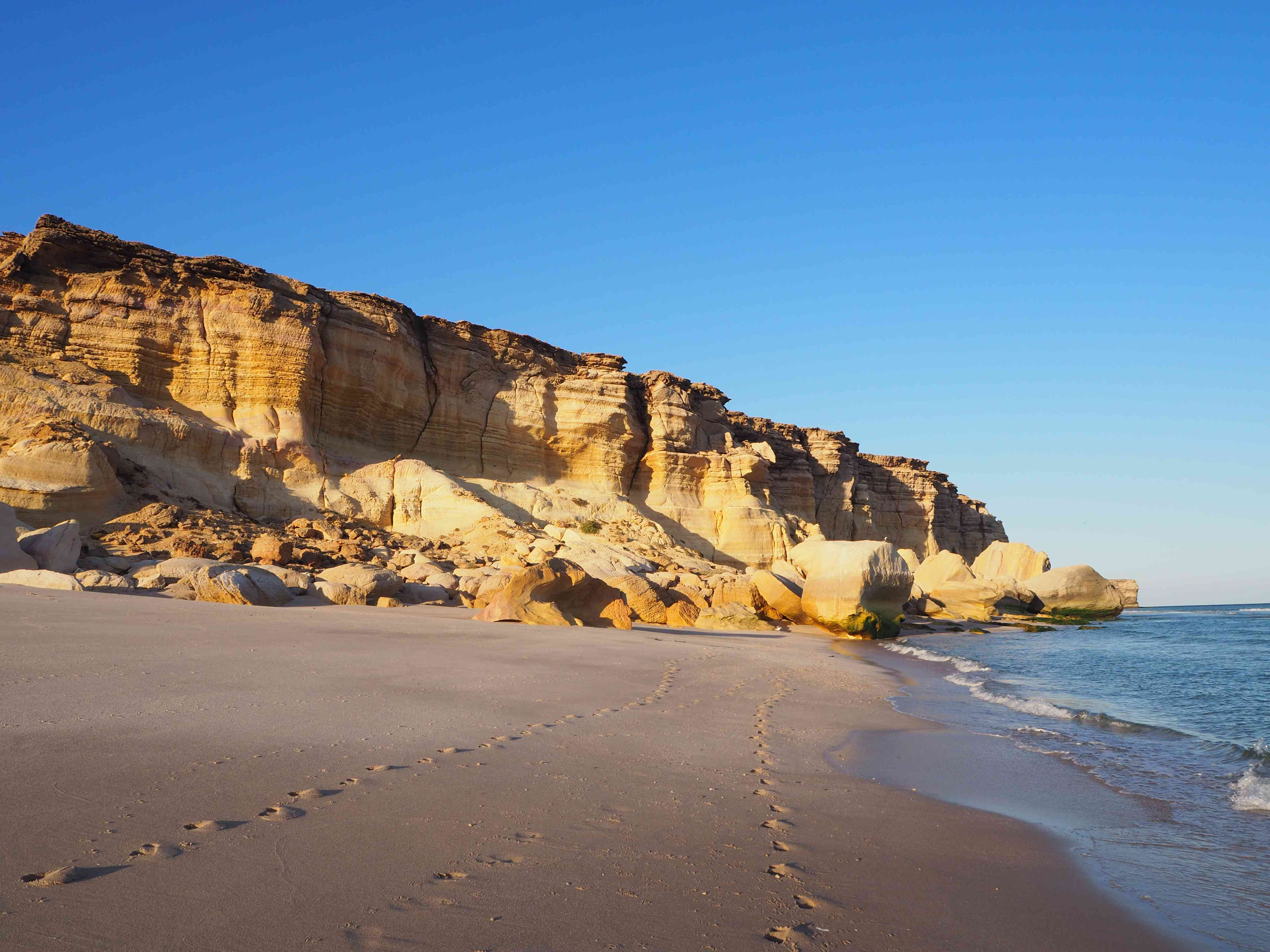 two sets of footprints on a beach in Oman with stone cliffs in the distance