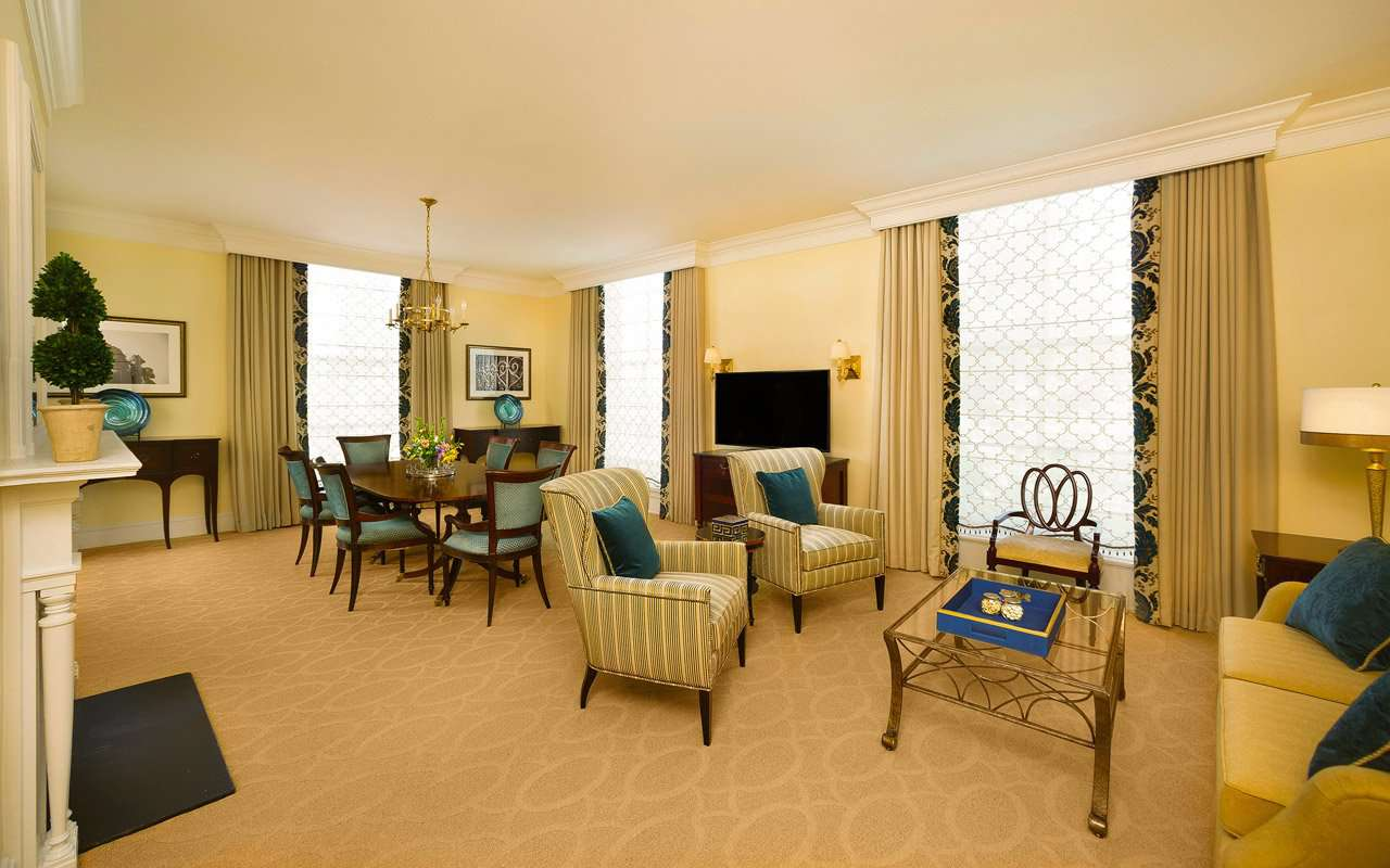 Hotel suite with dining table and living area with chair