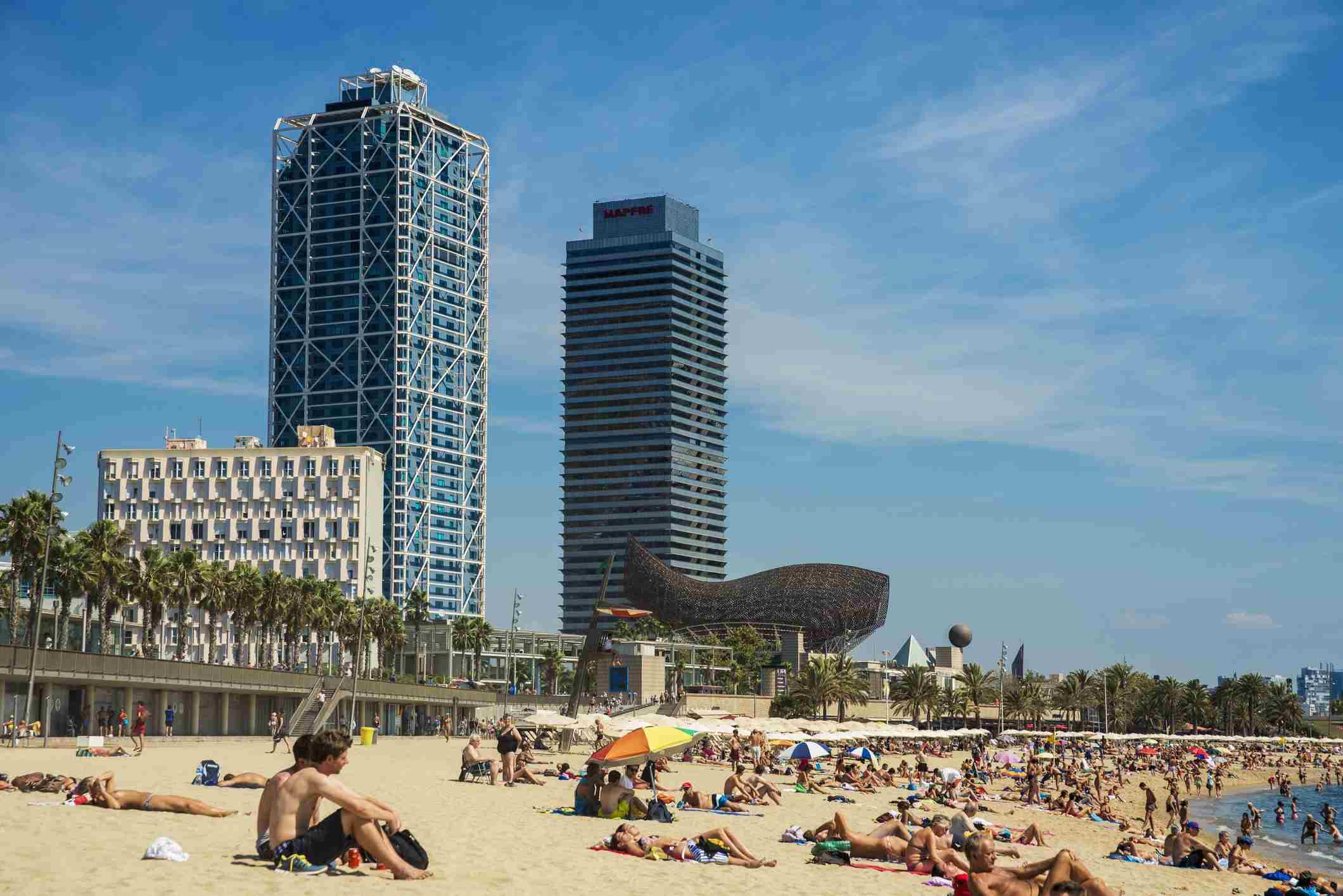 Una concurrida playa de la Barceloneta con rascacielos en la distancia