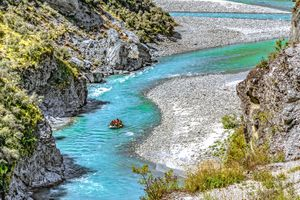 bright turquoise river winding through rocky landscape and a raft floating on it