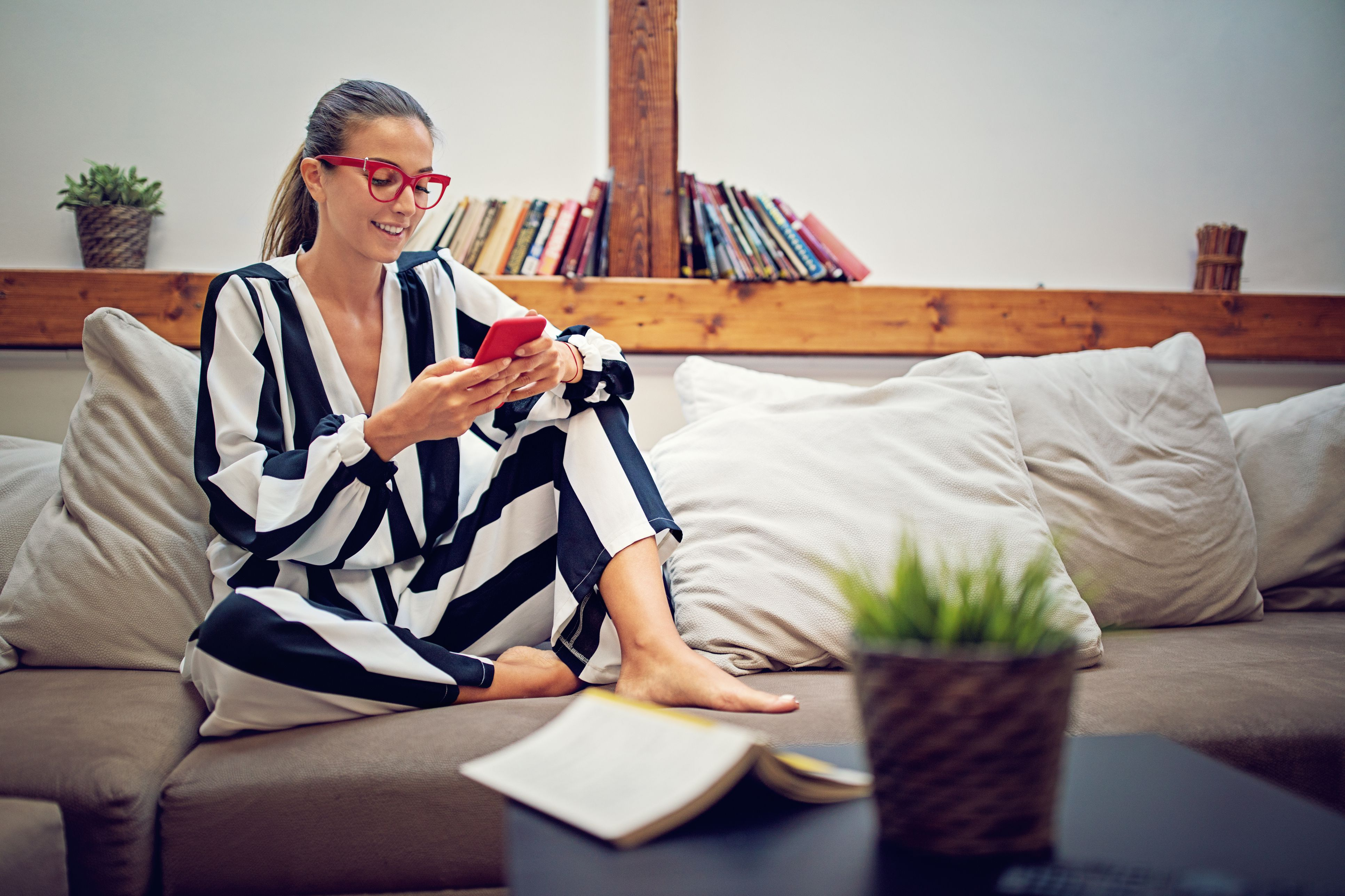 Young girl is sitting on the sofa and texting