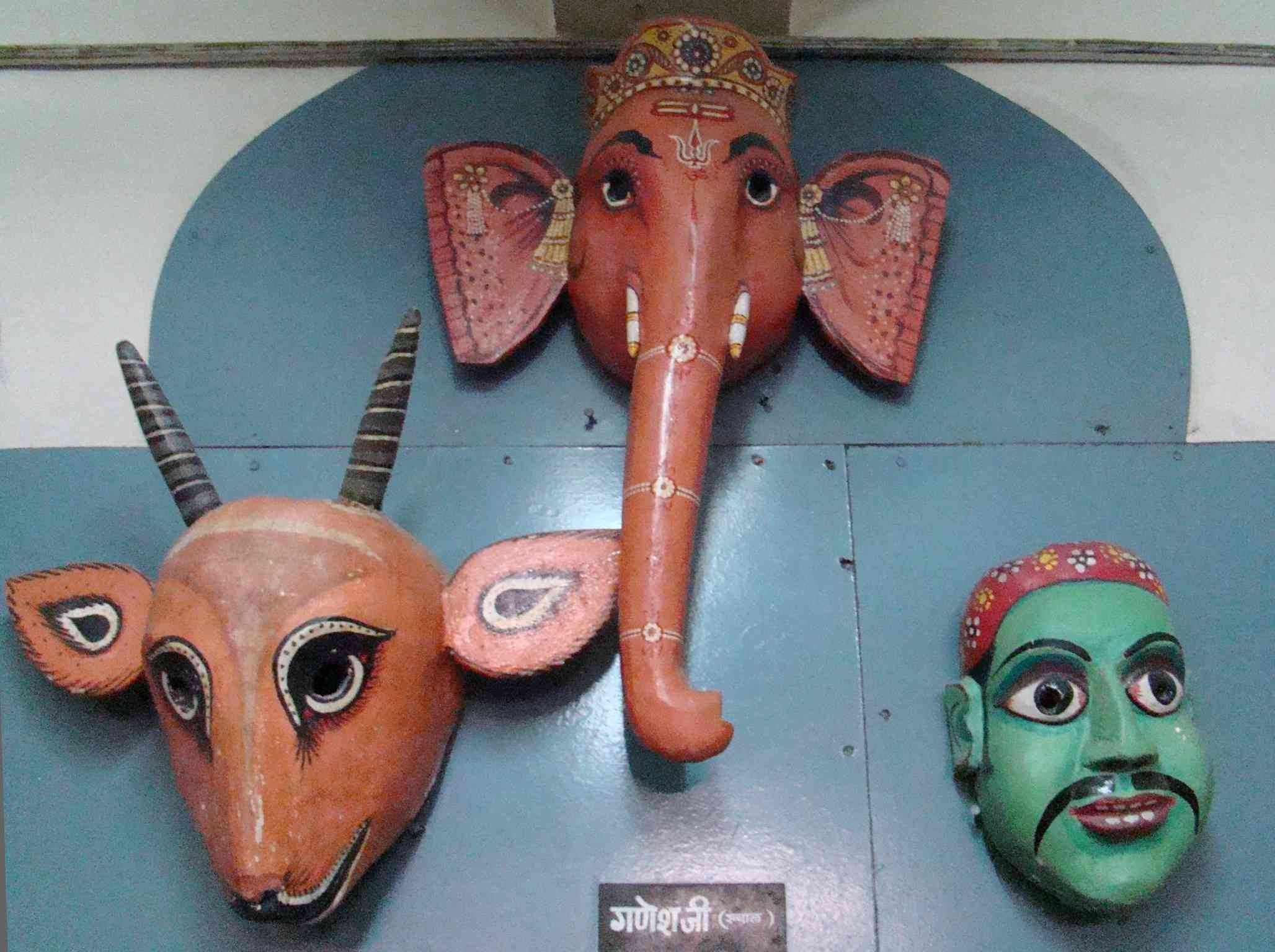 three masks (antelope, elephant, and green-faced man) hung on a wall