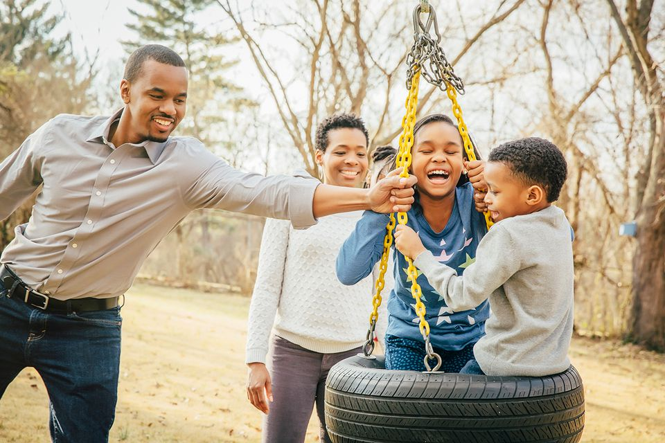 Black family playing on tire swing.
