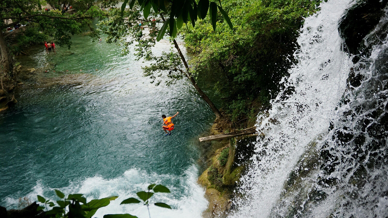 Vista de ángulo alto del hombre saltando en el río