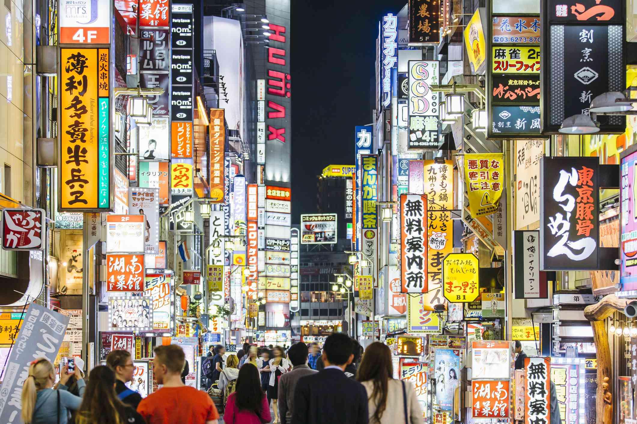 Crowds of people walking among illuminated neon signs at Kabukicho road in Shinjuku district, Tokyo, Japan