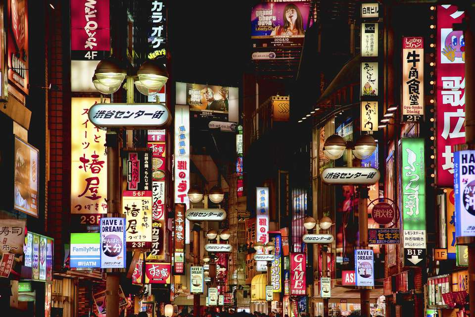 Center street in shibuya at night with dozens of illuminated signs