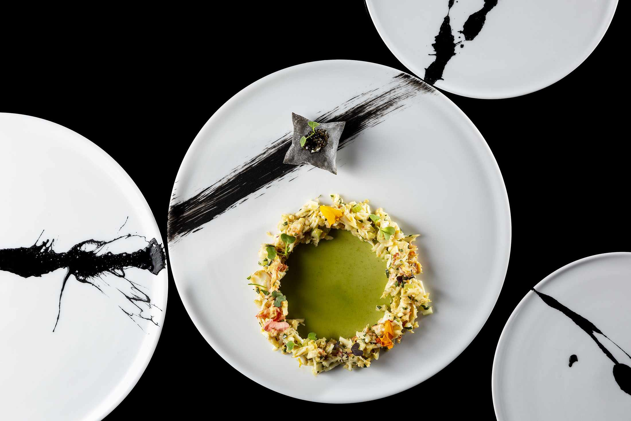 Gree alaskan king crab jelly crap on a black and white plate