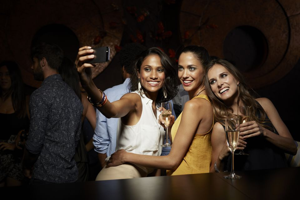 Happy women taking selfie at nightclub
