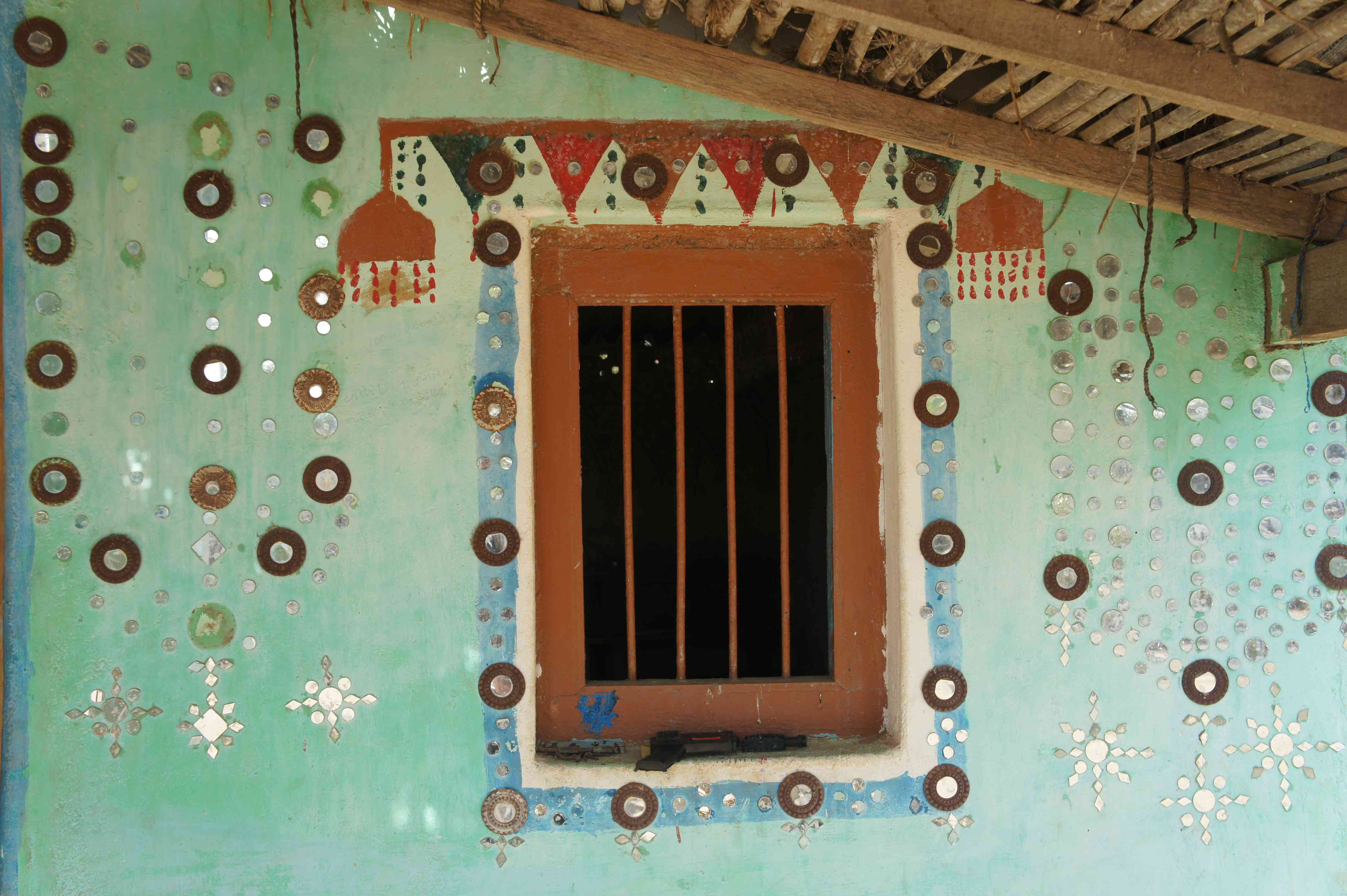 decorated wall of a house with small mirrows arranged artistically on a faded mint green wall