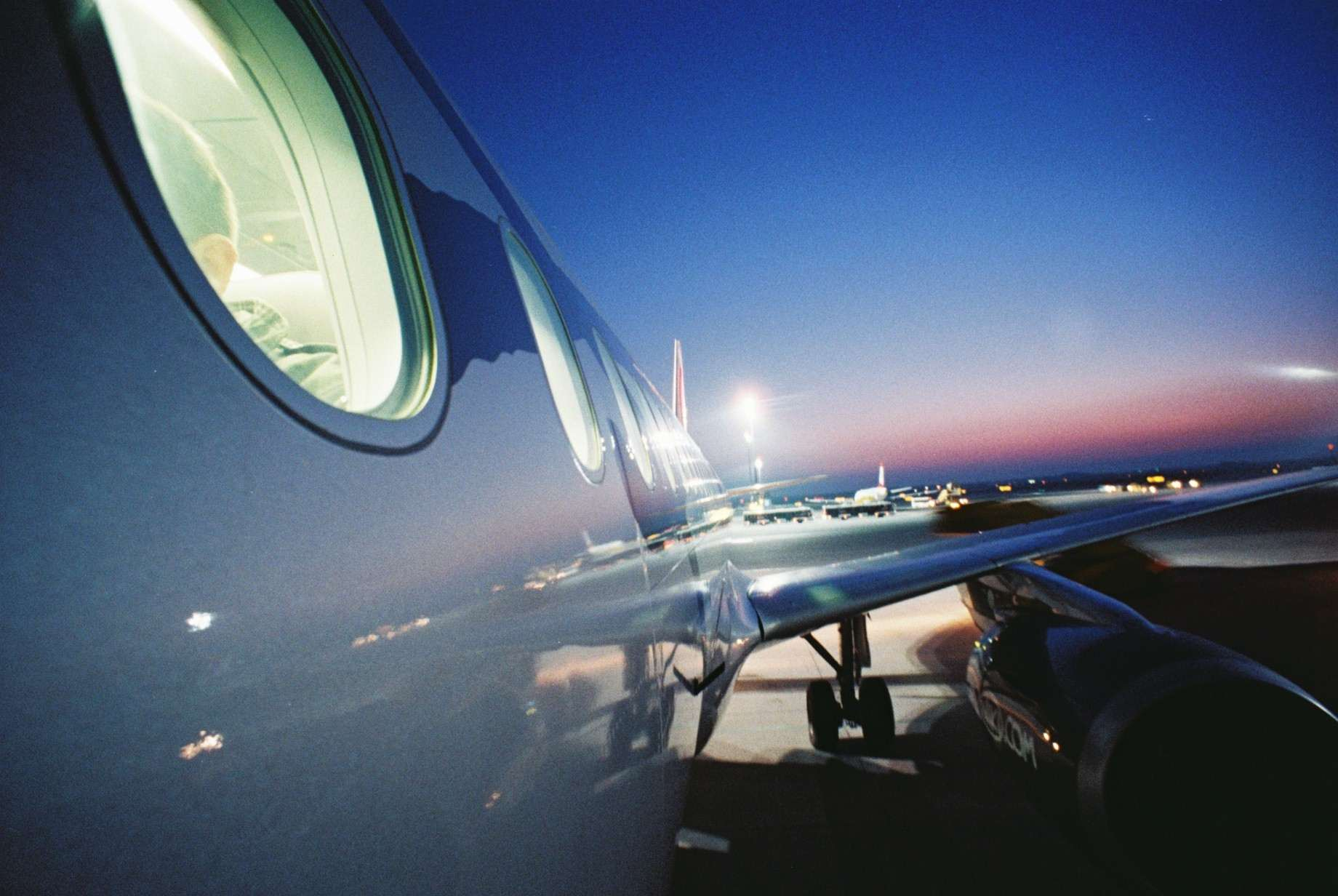 The side of an airplane at dusk.