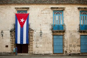 Young couple sharing a public kiss in front of the Cuban flag