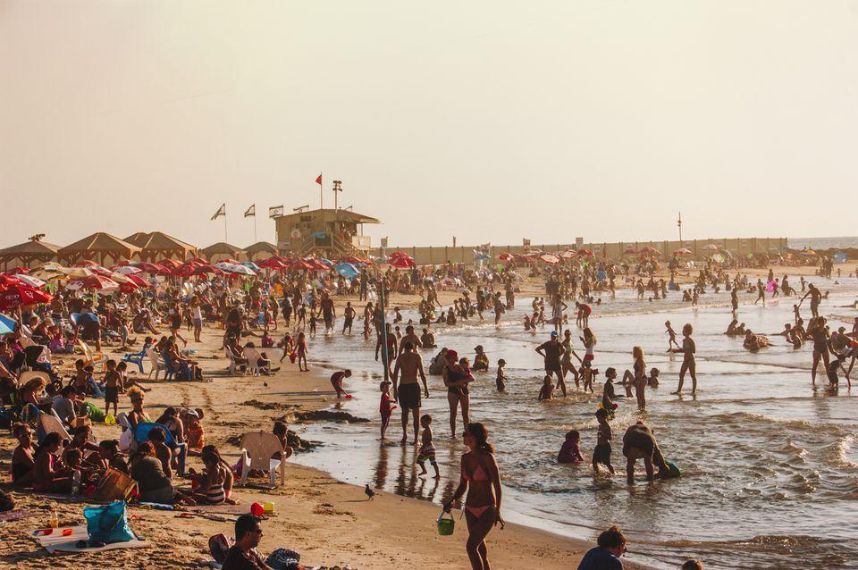 Playa llena de gente y puesta de sol en Tel Aviv