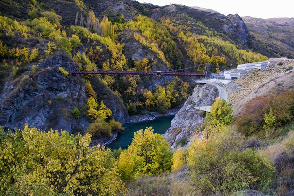 Kawarau bridge in Queenstown, New Zealand with yellow and green trees in the distance