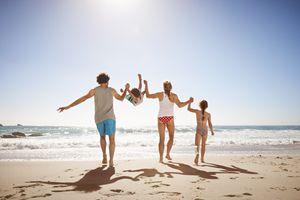Family of four having fun on the beach