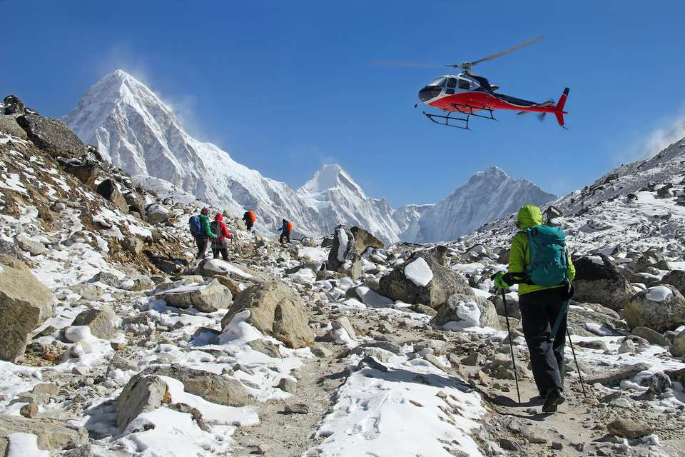 A helicopter hovers over trekkers in the Himalaya