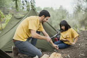 Camp counsellor and young camper tapping tent peg into ground