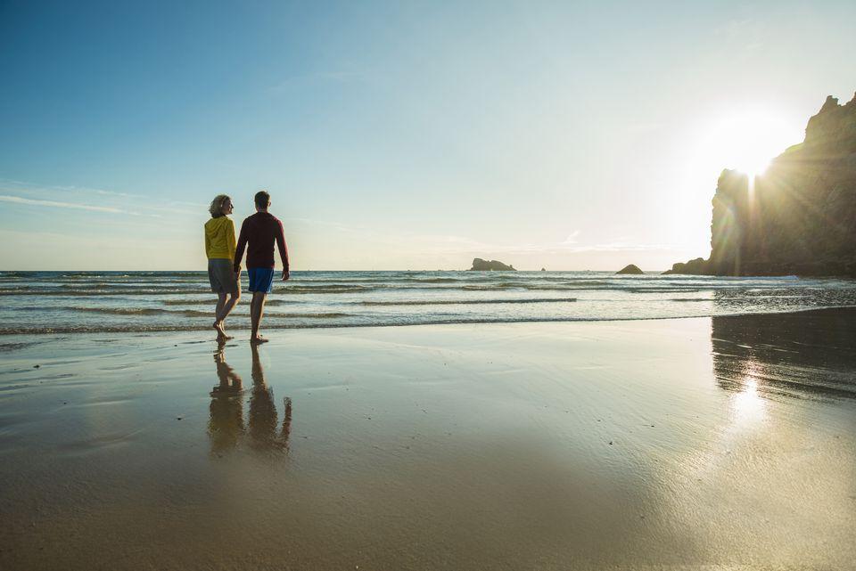 A couple walking on the beach near a calm ocean.