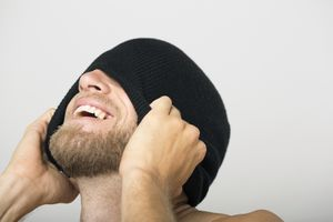 Laughing bearded man covering face with beanie