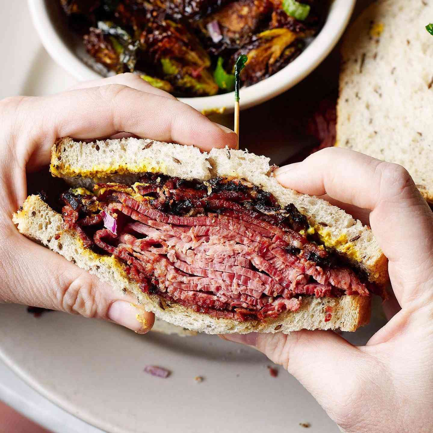 Pair of pale-skinned hands holding a reuben sandwich
