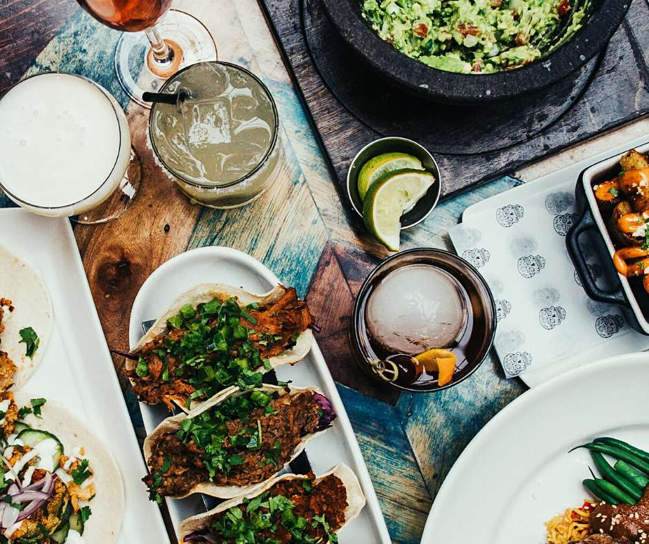 A table of vibrant Mexican dishes and cocktails