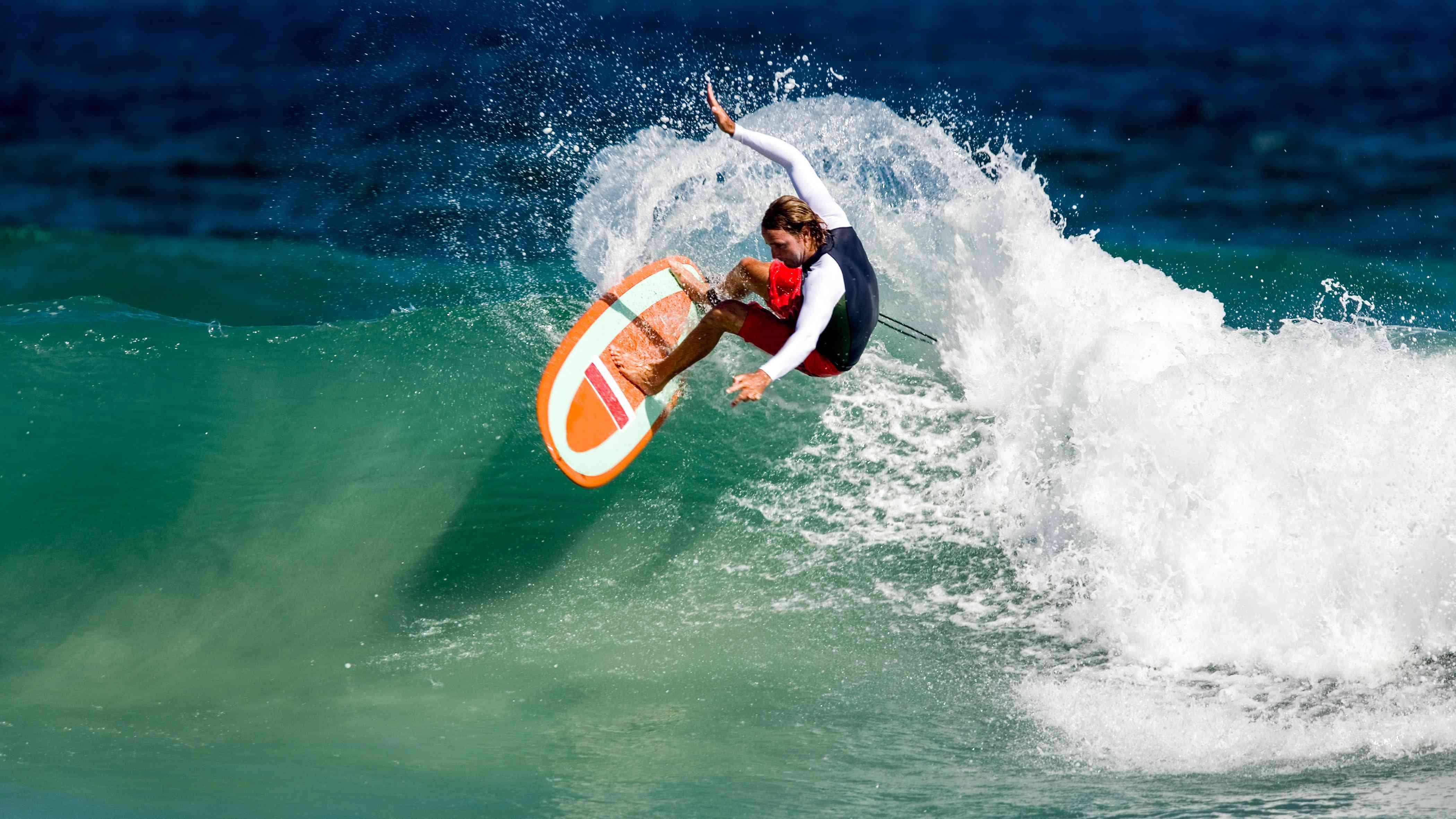 white man surfing a wave on Masirah Island