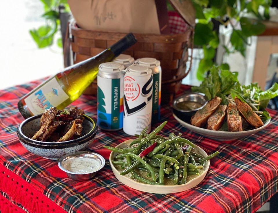 Mesa cubierta con una manta a cuadros con platos de pastel de carne, judías verdes y carne. Hay una botella de vino apoyada en una cerveza de cuatro lomos detrás de la comida y una cesta de picnic detrás del alcohol